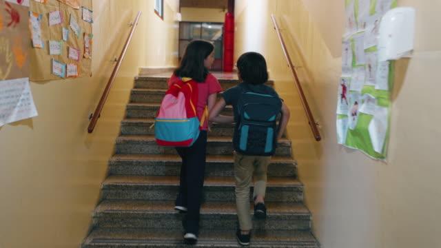 studenti della scuola primaria che camminano in classe - fianco a fianco video stock e b–roll