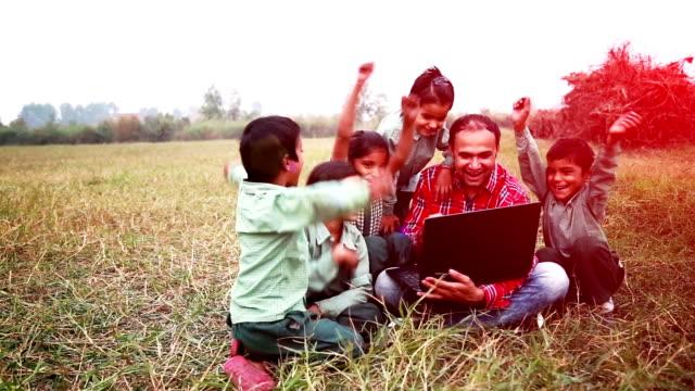 vidéos et rushes de les étudiants de l'école primaire professeur assis dans le champ tenant un ordinateur portable - extérieurs d écoles
