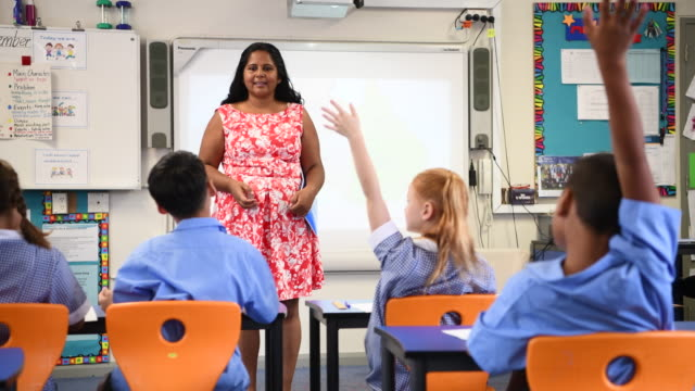 Primary school teacher talking to class as they raise their hands Aboriginal mid adult woman teaching class of primary school children and asking them questions elementary age stock videos & royalty-free footage