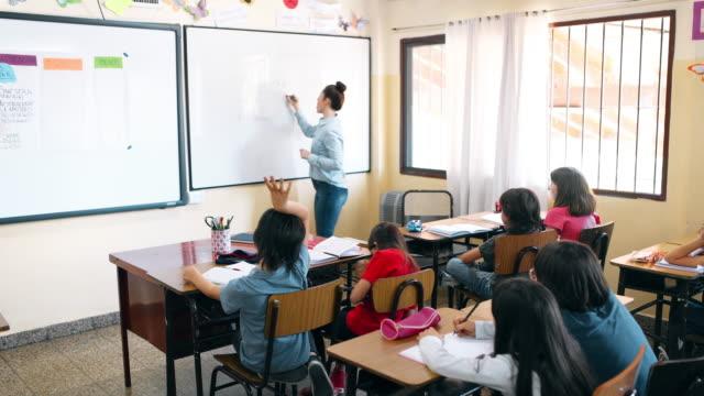 vídeos y material grabado en eventos de stock de profesor de escuela primaria que trabaja con los estudiantes en el aula - escuela primaria
