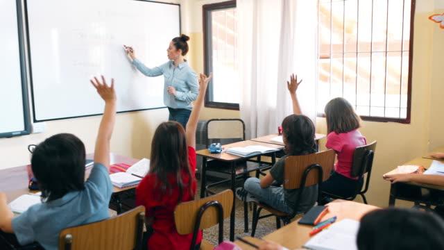 nauczyciel szkoły podstawowej pracujący z uczniami w classroom - instruktor filmów i materiałów b-roll