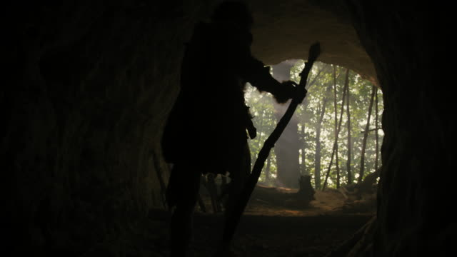 primeval caveman wearing animal skin and fur holds stone tipped spear comes out of his cave into prehistoric forest ready to hunt. neanderthal going hunting into the jungle - antica civiltà video stock e b–roll