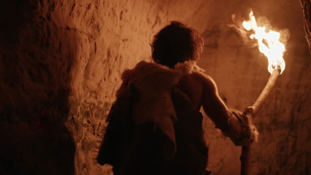 vídeos de stock e filmes b-roll de primeval caveman wearing animal skin exploring cave at night holding torch with fire looking at drawings on the walls at night. neanderthal searching safe place to spend the night. back view following - evolução
