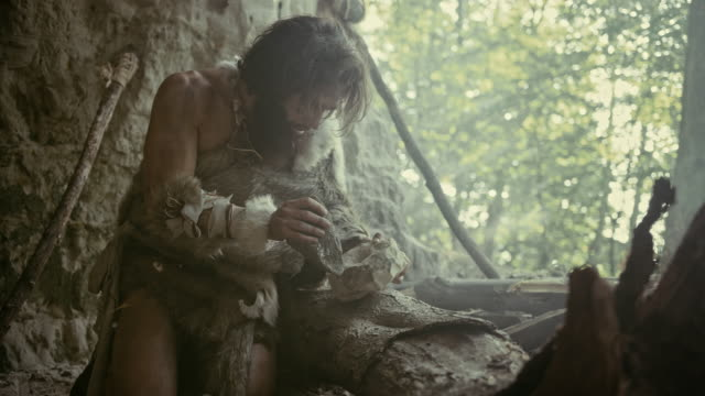 Primeval Caveman Wearing Animal Skin Hits Rock with Sharp Stone and Makes First Primitive Tool for Hunting Animal Prey or to Handle Hides. Neanderthal Using Handax. Dawn of Human Civilization