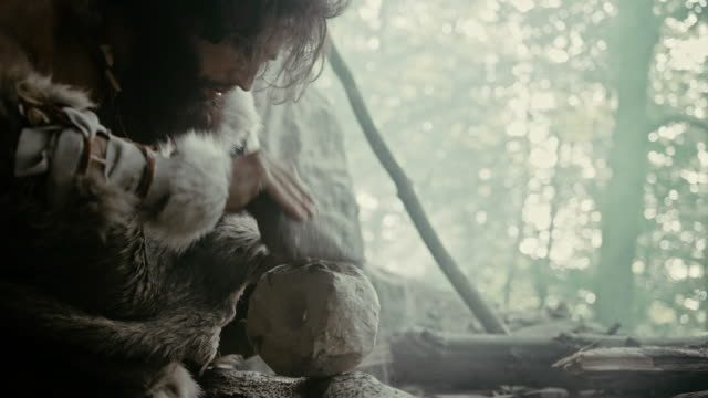 primeval caveman wearing animal skin hits rock with sharp stone and makes primitive tool for hunting animal prey. neanderthal using hand axe to create first wheel. slow motion shot - pietra roccia video stock e b–roll