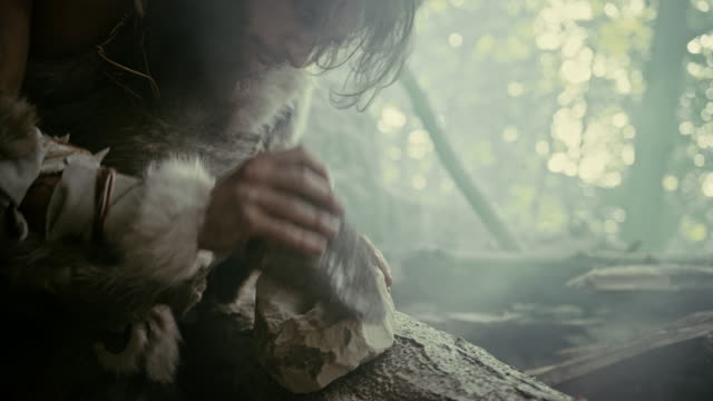 primeval caveman wearing animal skin hits rock with sharp stone, makes first primitive tool for hunting animal prey. neanderthal using flint rock. dawn of human civilization. slow motion closeup shot - pietra roccia video stock e b–roll
