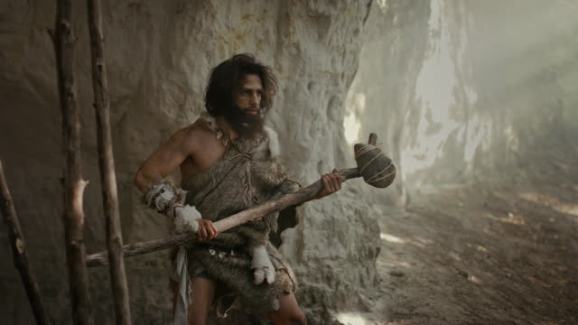 Primeval Caveman Wearing Animal Skin Holds Stone Tipped Hammer Comes out of the Cave and Looks Around Prehistoric Forest, Ready to Hunt Animal Prey. Neanderthal Going Hunting into the Jungle. Arc Shot