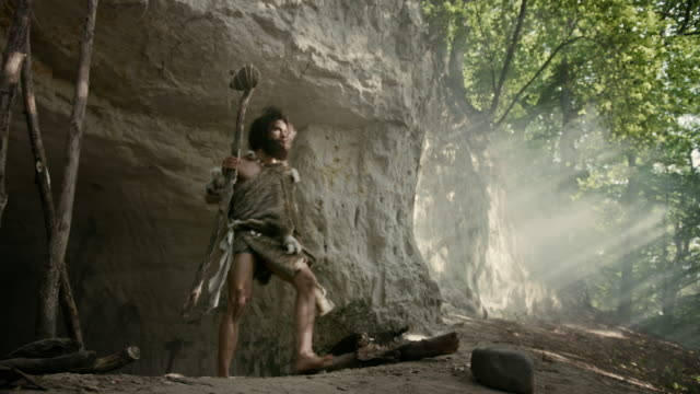 Primeval Caveman Wearing Animal Skin Holds Stone Tipped Hammer Looks Around Prehistoric Forest, Ready to Hunt Animal Prey. Neanderthal Going Hunting into the Jungle. Arc Shot video