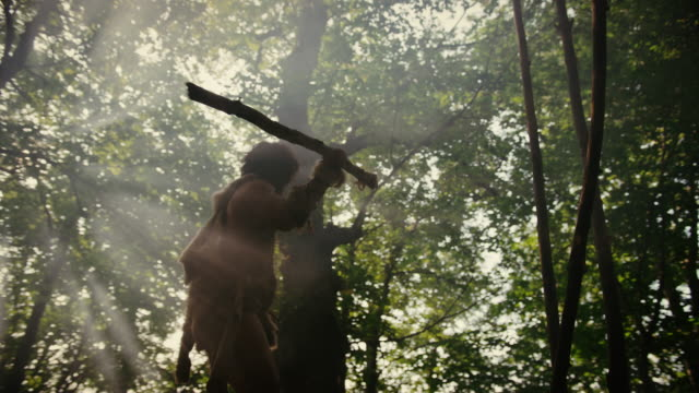primeval caveman wearing animal skin holds stone tipped spear looks around prehistoric forest, ready to hunt animal prey. neanderthal going hunting into the jungle. low angle slow motion arc shot - antica civiltà video stock e b–roll