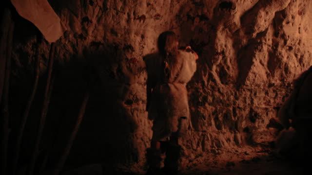 primitiva förhistoriska neandertalare barn bär djur hud drar djur och abstracts på väggarna på natten. skapa första grottkonst med hällristningar, sten målningar. tillbaka se följande bild - fornhistorisk tid bildbanksvideor och videomaterial från bakom kulisserna