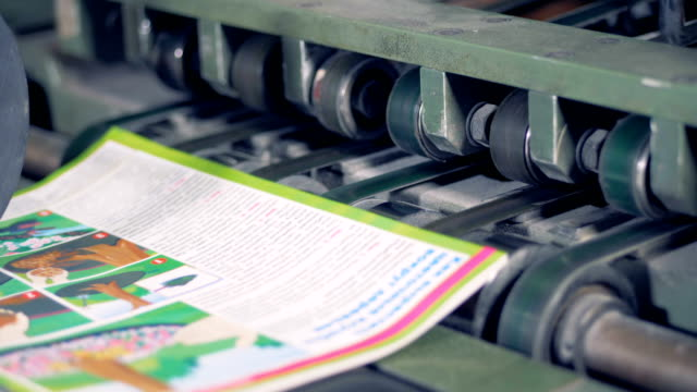 Printed books go on a conveyor, close up. New brochures move on a conveyor with the help of little rollers. printmaking technique stock videos & royalty-free footage