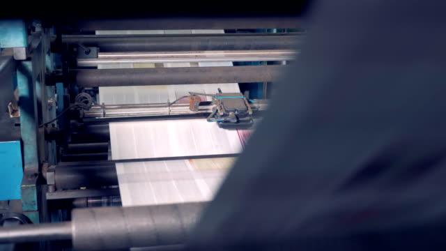 tryckta tidningar rullande på skrivarutrustning. - paper mass bildbanksvideor och videomaterial från bakom kulisserna