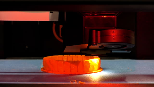 3D printer making red detail Close up of working 3D printer head printing orange red round detail printmaking technique stock videos & royalty-free footage