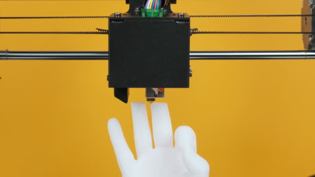 3D printer prints model hands fingers ok sign made of white plastic closeup on yellow background. Clear movements of print head and printer working platform. Potential of modern 3D printing technology 3D printer prints model hands fingers ok sign made of white plastic closeup on yellow background. Clear movements of print head and printer working platform. Potential of modern 3D printing technology scientific imaging technique stock videos & royalty-free footage