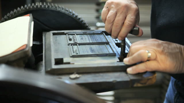 printer tightens letterpress type in a chase video