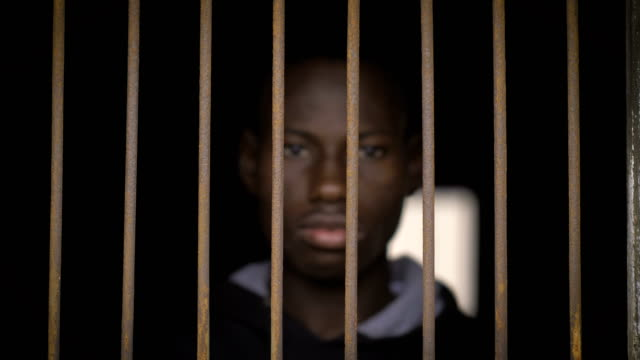 prison, crime, legality.young black african man behind bars - prigione video stock e b–roll