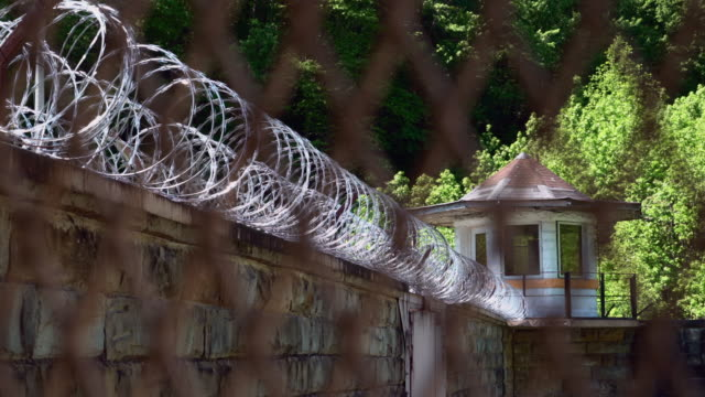 prison guard tower and razor wire - struttura pubblica video stock e b–roll