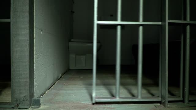 4k: prison / jail cell door closing shut - prigione video stock e b–roll