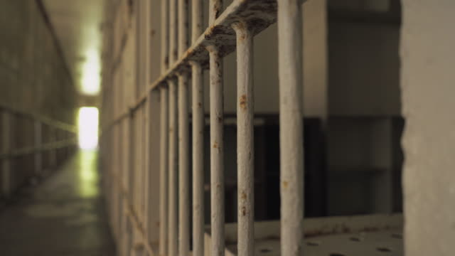 Prison Jail Cells Inside Penitentiary Looking down hallway at penitentiary at rows of inmate jail cells and bars. sentencing stock videos & royalty-free footage