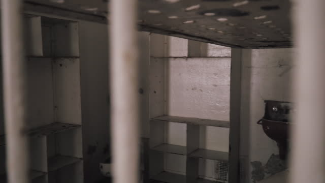 Prison Jail Cells Inside Penitentiary Looking down hallway at penitentiary at rows of inmate jail cells and bars. prison bars stock videos & royalty-free footage