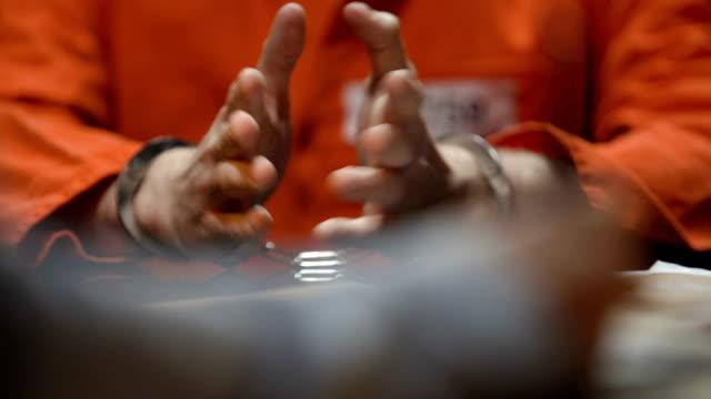 Prisoner giving evidence in interrogation room, detective writing testimony