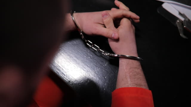 Prisoner in interrogation room with detective Two people, detective interrogating a man prisoner in dark investigation room, part of. police interview stock videos & royalty-free footage