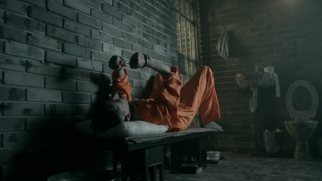 A prisoner lying on his bed in a prison cell video