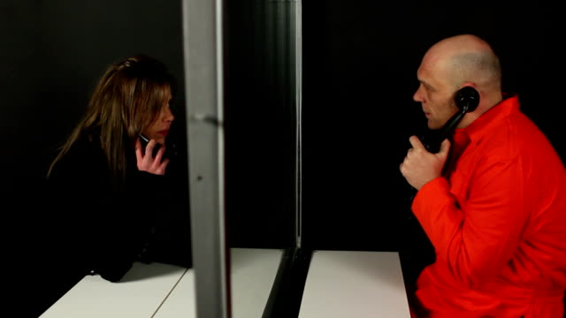 Prisoner talks to visitor on phone through glass video