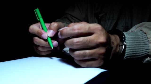 4k fångar är att underteckna en bekännelse på papper - fånga bildbanksvideor och videomaterial från bakom kulisserna