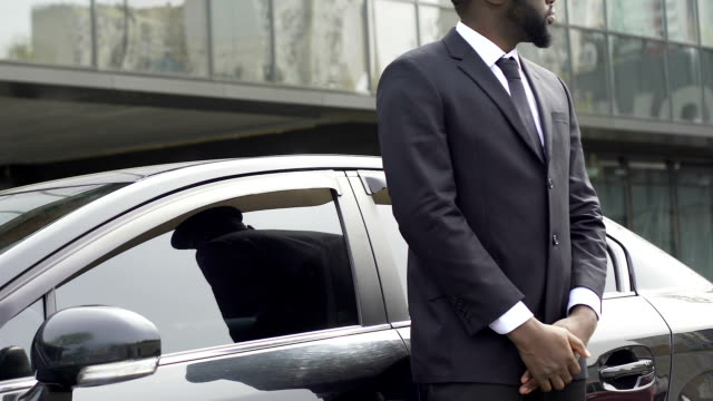 Private driver and bodyguard standing near car waiting for rich vip client