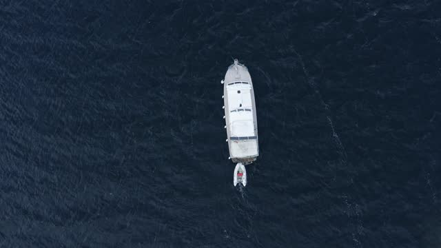 Private white yacht with a boat on the surface of dark seawater. Small waves on the sea aerial view slide.