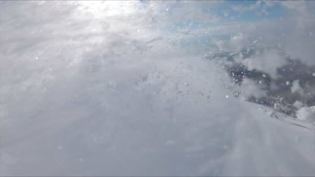 AERIAL: Pro freerider leaves a trail of snow behind him as he carves downhill.