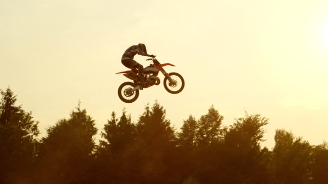 slow motion: pro freestyle motocross biker jumping extreme trick over the sun - freestyle motocross video stock e b–roll