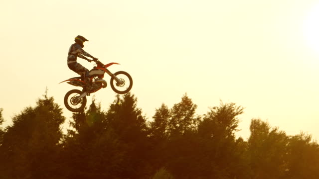 slow motion: pro freestyle motocross biker jumping superman trick over the sun - freestyle motocross video stock e b–roll