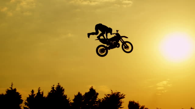slow motion: pro motocross biker jumping no hands superman against sunset sky - motocross video stock e b–roll