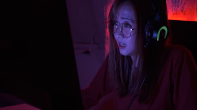 Pro player gamer young asian woman playing online video game shooting fps tournament ranking cyber internet at night red neon light room with gaming on championship event handheld shot 4k UHD.