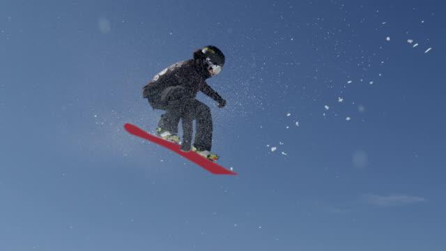 スローモーションクローズアップ:プロのスノーボーダージャンプな空気の流れを上手く汲んで、スノーボードコンテスト - スポーツ用品点の映像素材/bロール