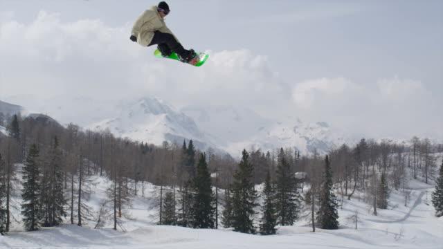 AERIAL SLOW MOTION: Pro snowboarder jumping big air kicker video