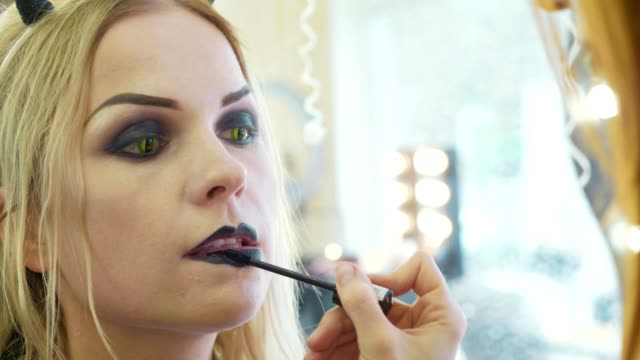 vídeos de stock e filmes b-roll de process applying halloween makeup on face the young beautiful woman - contacts