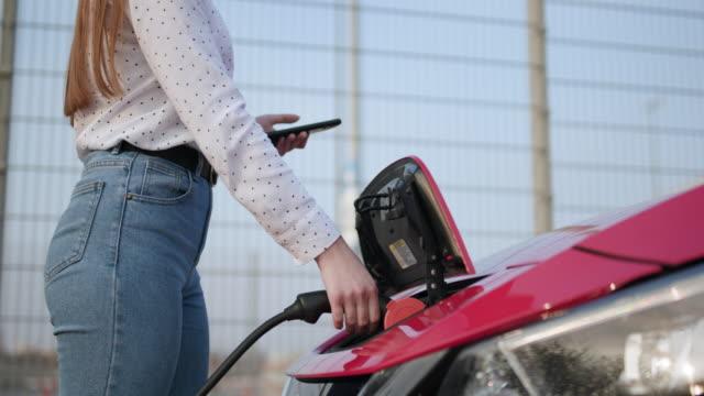 il processo di ricarica elettrica dell'auto termina. ragazza caucasica che usa lo smartphone e l'alimentatore in attesa si collega ai veicoli elettrici - carica elettricità video stock e b–roll