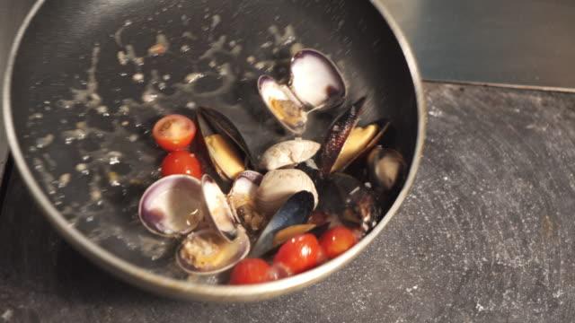 vídeos de stock, filmes e b-roll de processo de cozinhar massa italiana com mexilhões ao molho de tomate. cozinhe a massa na panela. - comida italiana
