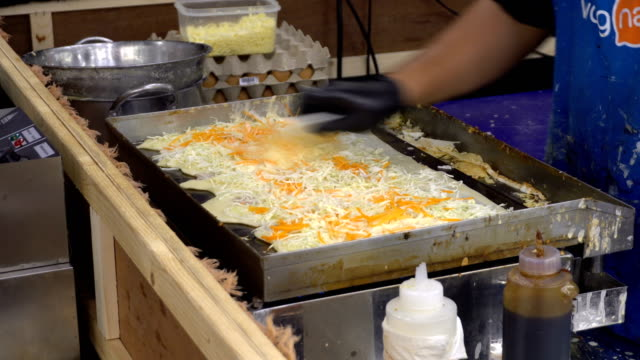 Process of cooking okonomiyaki roll on traditional bamboo mats. Japanese pizza