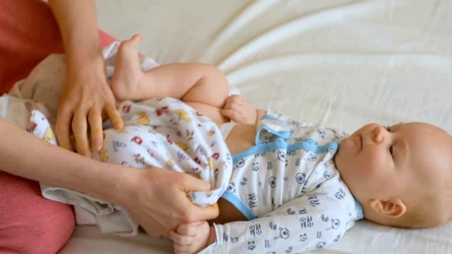process of dressing little baby - abbigliamento da neonato video stock e b–roll