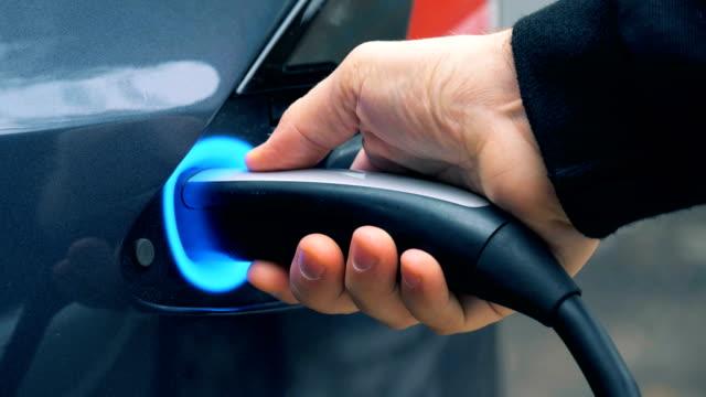 process of electric car charging, close up. - carica elettricità video stock e b–roll