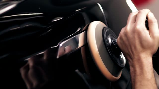 processen av efterbehandling polering av en ny svart bildörr. - skinande bildbanksvideor och videomaterial från bakom kulisserna