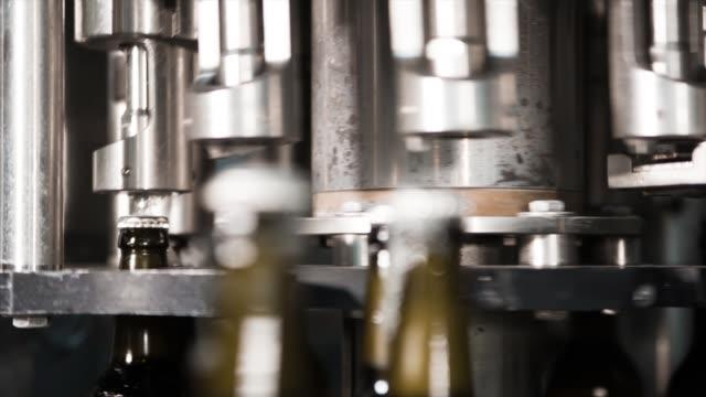 ガラスのビール瓶に金属製のカバーをインストールするプロセス。 - 醸造所点の映像素材/bロール