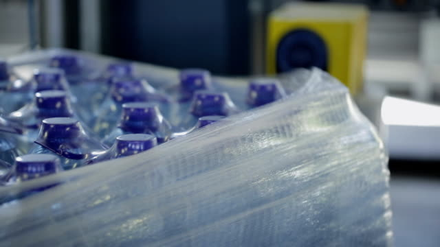 vídeos de stock e filmes b-roll de process of packaging plastic bottles with water on conveyor belt in factory - packaging
