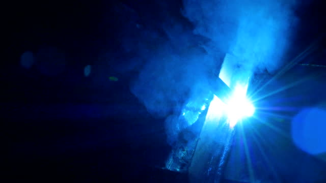 Process of welding at a factory, close up. A welding machine works in dark. welder stock videos & royalty-free footage