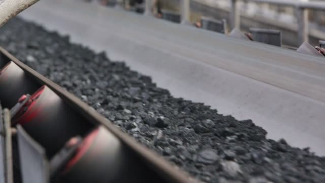 processed coal on conveyor belt - close up Processed and refined coal travels on a conveyor belt ready for transport by rail at an open pit coal mine.  Close up. power stock videos & royalty-free footage