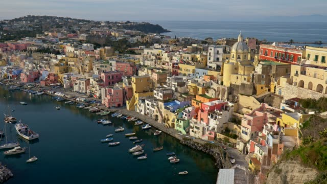 procida island, italy. panoramic shot of multi-colored buildings and yellow church. boats moored by coast of tyrrhenian sea. uhd - procida video stock e b–roll